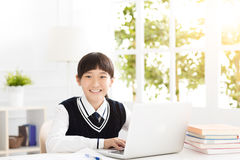 Glücklicher Jugendlicher Student, der mit Laptop studiert stockfotos