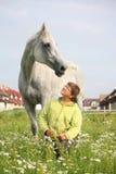 Glücklicher Jugendlichjunge und weißes Pferd am Feld Stockbilder