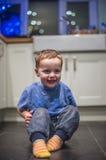 Glücklicher Junge auf Küchenboden lizenzfreie stockbilder
