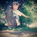 Glücklicher Junge auf Schwingen Stockfotos