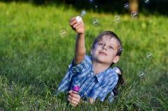 Glücklicher Junge beginnt oben Seifenluftblasen Stockbilder