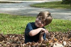 Glücklicher Junge in den Blättern Stockfotografie