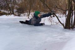 Glücklicher Junge, der auf dem Eis am Nachmittag im Winter liegt stockbild