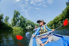 Glücklicher Junge, der auf dem Fluss an einem sonnigen Tag während der Sommerferien Kayak fährt Lizenzfreies Stockfoto