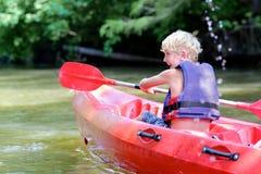 Glücklicher Junge, der auf dem Fluss Kayak fährt Stockbild