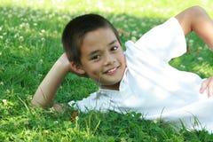 Glücklicher Junge, der auf grünem Gras liegt Lizenzfreies Stockfoto