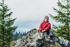 Glücklicher Junge, der auf Klippe steht Stockfotos
