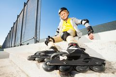 Glücklicher Junge, der auf der Treppe in den Rollschuhen sitzt Stockfotos