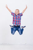 Glücklicher Junge, der auf weißen Hintergrund springt Stockfotografie