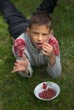 Glücklicher Junge, der Beeren auf dem Gras isst Stockbild