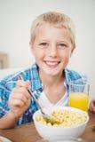 Glücklicher Junge, der bei Tisch im Haus frühstückt Lizenzfreie Stockfotografie