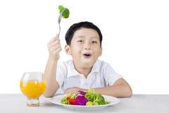 Glücklicher Junge, der Brokkoli isst stockfotografie
