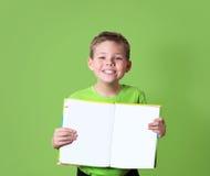 Glücklicher Junge, der Buch mit leerem Kopienraum hält getrennte alte Bücher Stockbild