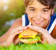Glücklicher Junge, der Burger isst stockbild