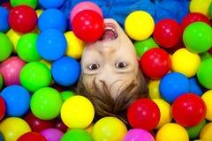 Glücklicher Junge, der in den bunten Bällen spielt Glückliches Kind, das an der hohen Ansicht des bunten Plastikballspielplatzes  stockbild