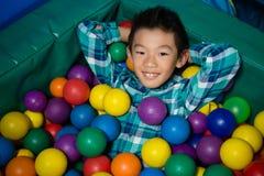 Glücklicher Junge, der in den bunten Bällen während der Geburtstagsfeier liegt stockfotos