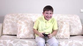 Glücklicher Junge, der die Videospiele, slowmotion spielt stock video