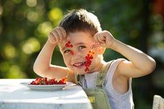 Glücklicher Junge, der eine rote Johannisbeere hält Lizenzfreie Stockfotos