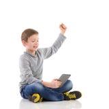 Glücklicher Junge, der eine Tablette verwendet. Stockbild
