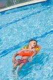 Glücklicher Junge, der in einem funkelnden Pool sich entspannt stockfotografie