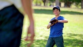 Glücklicher Junge, der einen Baseball beim Tragen eines Handschuhs fängt stock video