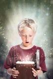 Glücklicher Junge, der einen Geschenk-Kasten öffnet Stockfotografie