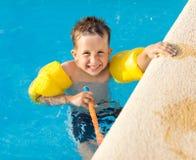 Glücklicher Junge, der einen Spaß am Swimmingpool hat stockfoto