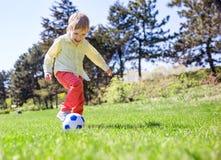 Glücklicher Junge, der Fußball spielt lizenzfreies stockfoto