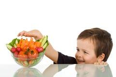 Glücklicher Junge, der Gemüse stiehlt stockfotografie
