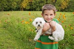Glücklicher Junge, der Hund hält Lizenzfreie Stockbilder
