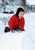 Glücklicher Junge, der im Schnee spielt Stockfoto