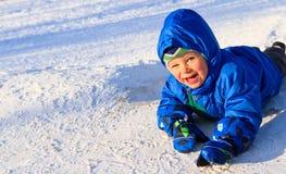 Glücklicher Junge, der im Schnee spielt Stockfotografie