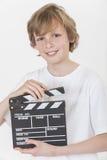 Glücklicher Junge, der mit Clapperboard lächelt stockfotos