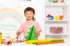 Glücklicher Junge, der Perlen und Karton Weihnachtsbaum hält Stockfotos