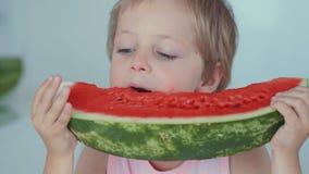 Glücklicher Junge, der rote Wassermelone und den Saft fließt unter die Zähne isst stock video