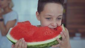 Glücklicher Junge, der rote Wassermelone und den Saft fließt unter die Zähne isst stock footage