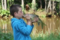 Glücklicher Junge, der seine Fische auf dem Mund küßt Stockbild