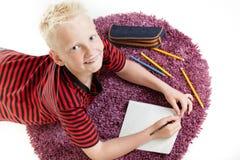 Glücklicher Junge, der an seiner Hausarbeit arbeitet Stockfoto