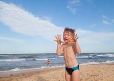 Glücklicher Junge, der Spaß auf dem Hintergrund von Meer hat Stockfotos
