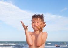Glücklicher Junge, der Spaß auf dem Hintergrund von Meer hat Lizenzfreie Stockbilder