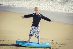 Glücklicher Junge, der Spaß am Strand im Urlaub hat, lizenzfreies stockbild