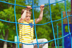 Glücklicher Junge, der am Spielplatz im Sommer spielt Stockfoto