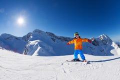 Glücklicher Junge in der Sturmhaube mit den Armen auseinander allein Ski fahrend stockfoto