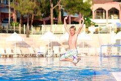 Glücklicher Junge, der in Swimmingpool springt Lizenzfreie Stockfotografie