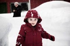 Glücklicher Junge in einer roten Jacke an einem Snowy-Tag Lizenzfreie Stockfotografie