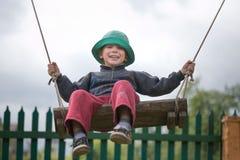 Glücklicher Junge fährt auf ein Schwingen Lizenzfreie Stockfotos