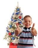 Glücklicher Junge gegen einen Weihnachtsbaum stockbild