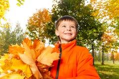 Glücklicher Junge hält Bündel Leuchtorangeblätter Stockfotos