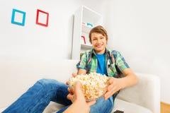 Glücklicher Junge hält Popcornschüssel von jemand Hand Stockbild