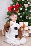 Glücklicher Junge im Rotwildkostüm mit Geschenkboxen und Weihnachtsbaum Stockfotografie